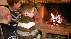 Two sons and father sitting near fireplace Stock Footage