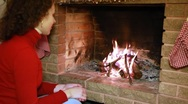 Woman sits by fireplace watch fire Stock Footage