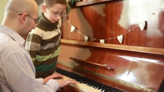 Son and father  in glasses playing piano Stock Footage