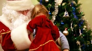 Santa Claus gives gifts to girl near Christmas tree Stock Footage