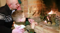 Father and son sitting near fireplace Stock Footage