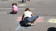 The Small children draw the colour piece of chalk on asphalt - stock footage