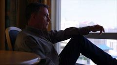 Man sitting by a window thinking Stock Footage