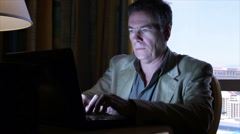 Man typing on laptop in dimmly light room Stock Footage