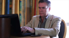 Man on laptop answers cell phone Stock Footage