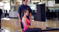 Stock Video Footage of Personal Trainer Instructs Young Woman on Using Exercise Ball