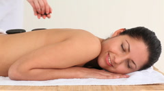 Brunette having a treatment with hot stones Stock Footage