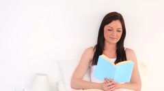 Attractive woman reading a novel Stock Footage