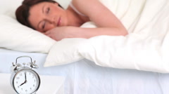 Alarm clock ringing while a cute woman is sleeping - stock footage