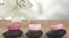 Candles raised on pebbles being lighted Stock Footage