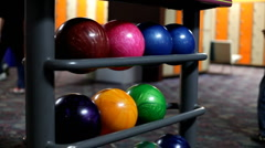 People walking by rack of bowling balls Stock Footage