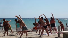 Tourists making  aerobics on beach Stock Footage