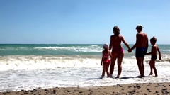 Parents and children standing hand in hand, then run into the sea Stock Footage
