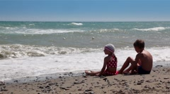 Two children looking at the waves and throw rocks into the water - stock footage