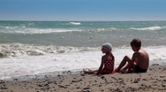 Stock Video Footage of Two children looking at the waves and throw rocks into the water