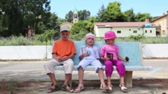 Three children sitting on the bench Stock Footage