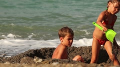 Two children are in a small pit in the sand before the water Stock Footage