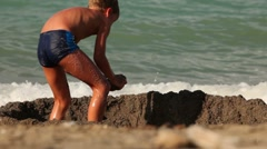 The boy digs a hole in the sand - stock footage