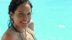 Young woman sitting in hotel swimming pool for holiday - stock footage