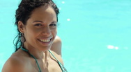 Stock Video Footage of Young woman sitting in hotel swimming pool for holiday