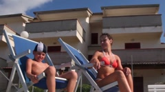 Mother and son sitting in deckchairs, then boy jumps to pool water Stock Footage