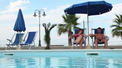 Couple sitting in deckchairs in front of the pool Stock Footage