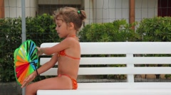 Little girl are sitting on bench with colored toy in hands Stock Footage