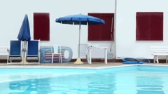 Parasols, chairs and other things are on edge of the pool Stock Footage
