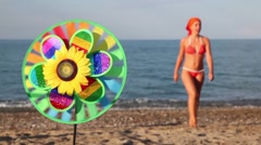 Toy with sunflower in center, that spins on the background of sea and woman Stock Footage