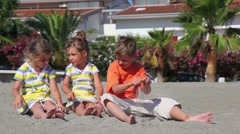 Tree kids boy and two girls sitting on sand - stock footage