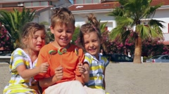 Tree kids sitting on sand and showing lolly candy to each other Stock Footage