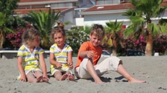 Two children sitting on the sand and throw them against the house - stock footage