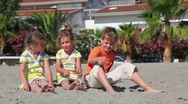 Stock Video Footage of Two children sitting on the sand and throw them against the house