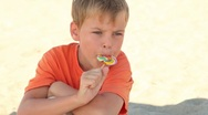 Stock Video Footage of The boy sitting on the sand and eating candy