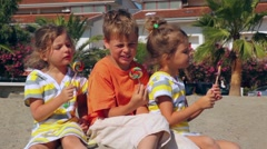 Tree kids eating lolly candy sitting on sand Stock Footage