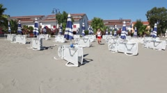 Woman runing closer by sand between lot of deckchairs Stock Footage
