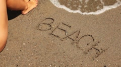 The word beach is written on the sand, sea wave appear Stock Footage