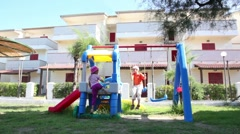 Two kids, boy and girl, on playground, boy is sways on swing - stock footage