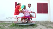 Stock Video Footage of Parents and daughter, rotating on a carousel