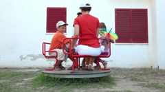 Parents and children sitting on a carousel, and begin to rotate - stock footage