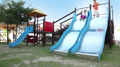 Two children are on playground object, boy sliding down - stock footage