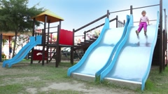 Two children are on playground object, both slide down Stock Footage