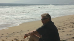 MAN REFLECTS AT BEACH Stock Footage