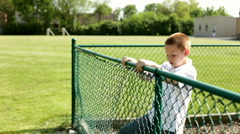Boy climbing over fence Stock Footage