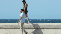 Young husband and wife during afternoon walk near the sea Stock Footage