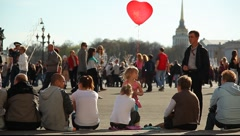 Sitting people. Girl with red balloon stay agains people Stock Footage