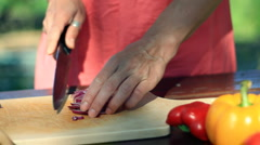Woman's hands chopping red onion, outdoors HD Stock Footage