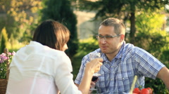 Happy couple drinking wine and talking in the garden, dolly shot HD - stock footage