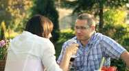 Stock Video Footage of Happy couple drinking wine and talking in the garden, dolly shot HD