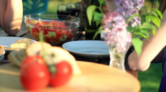 Family hands eating food from the table in the garden, dolly shot HD Stock Footage